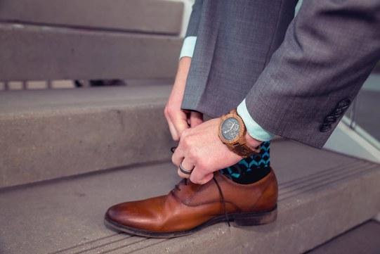 man wearing jord conway series walnut jet black unique wood watch tying steve madden shoe laces