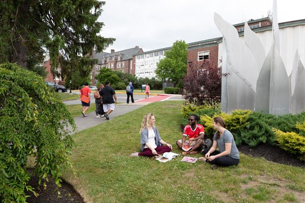 Students sitting in the grass at MassBay Community College