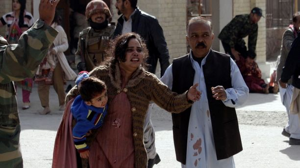 A man helps an injured woman and a child following an attack on a church in Quetta, Pakistan, Sunday, Dec. 17, 2017. Two suicide bombers attacked the church when hundreds of worshippers were attending services ahead of Christmas. (AP Photo/Arshad Butt)