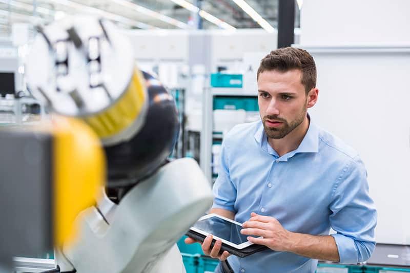 man using digital tablet standing at machine