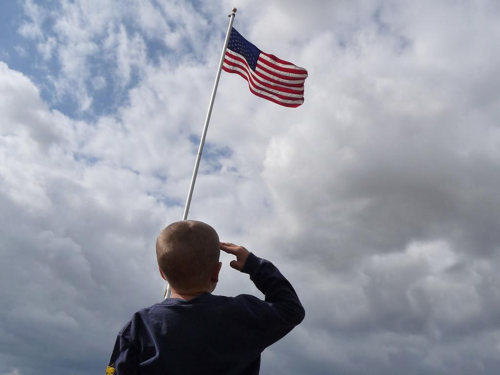 child saluting flag
