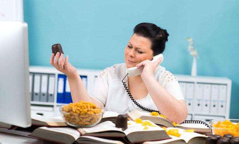 übergewichtige frau isst süßigkeiten bei der arbeit