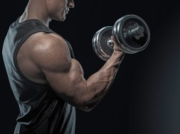 Close-up of a power fitness man doing biceps workout