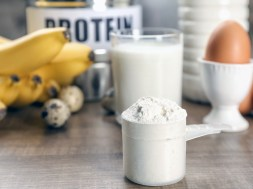 Scoop with protein powder and products on table
