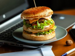 Eating at work place – fast food. burger near laptop. lunch brea