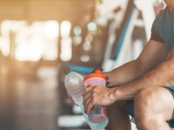 Cropped portait of young man sitting in gym and holding a bottle of water and a classic fitness shaker with pre-workout drink in it. Sports nutrition concept. Horizontal shot. Side view
