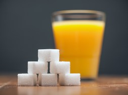 Amounts of Sugar In Food – Glass of Orange Juice, On wooden tabl