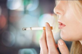 Portrait of the young elegant girl smoking cigarette isolated