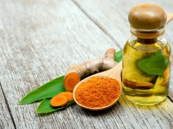 Turmeric essential oil and tumeric powder with green leaf isolat