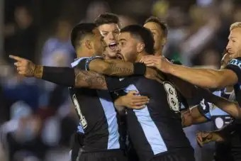 Andrew Fifita points while being hugged by teammates.