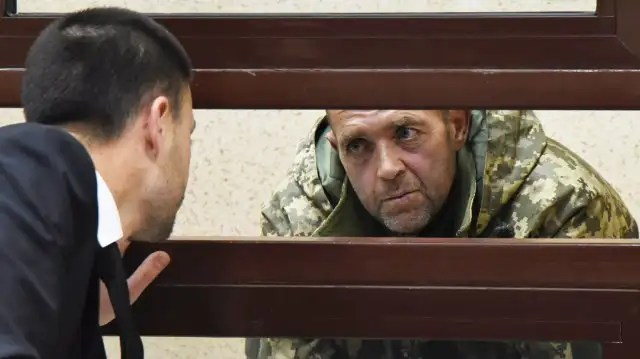 One of the captured Ukrainian sailors speaks with his lawyer in a Russian courtroom.