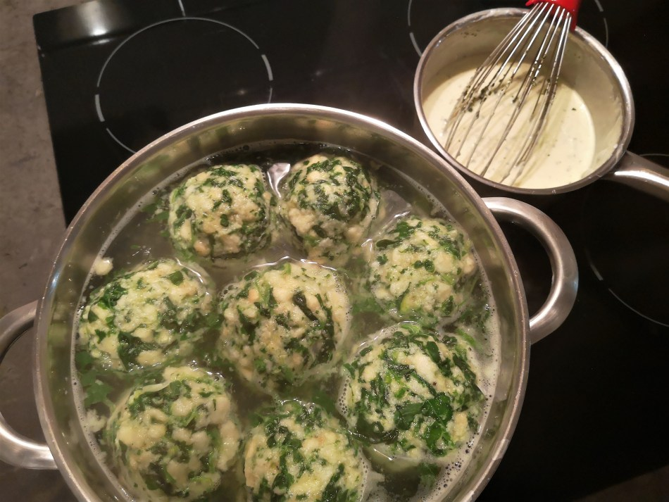 Acht Spinatknödel ziehen im Kochtopf - daneben steht ein Topf Käsesauce