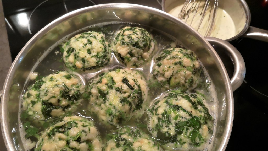 Acht Spinatknödel schwimmen im Kochtopf. Dahinter steht die fertige Käsesauce.