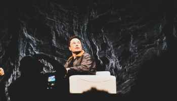 Elon Musk in a brown leather jacket on stage sitting and looking up.