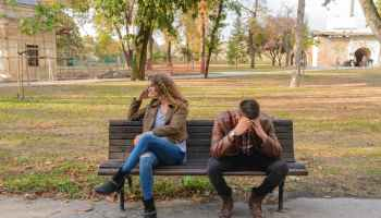 Couple sitting on brown wooden bench and having an argument.