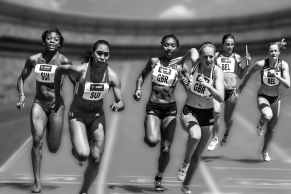 Black and white photo of women competing in a relay race at a track meet.