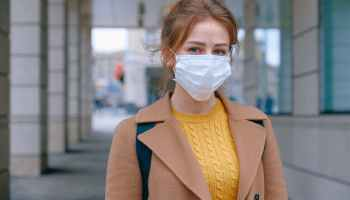 Woman in a yellow sweater and brown coat wearing face mask during the 2019-20 coronavirus pandemic.