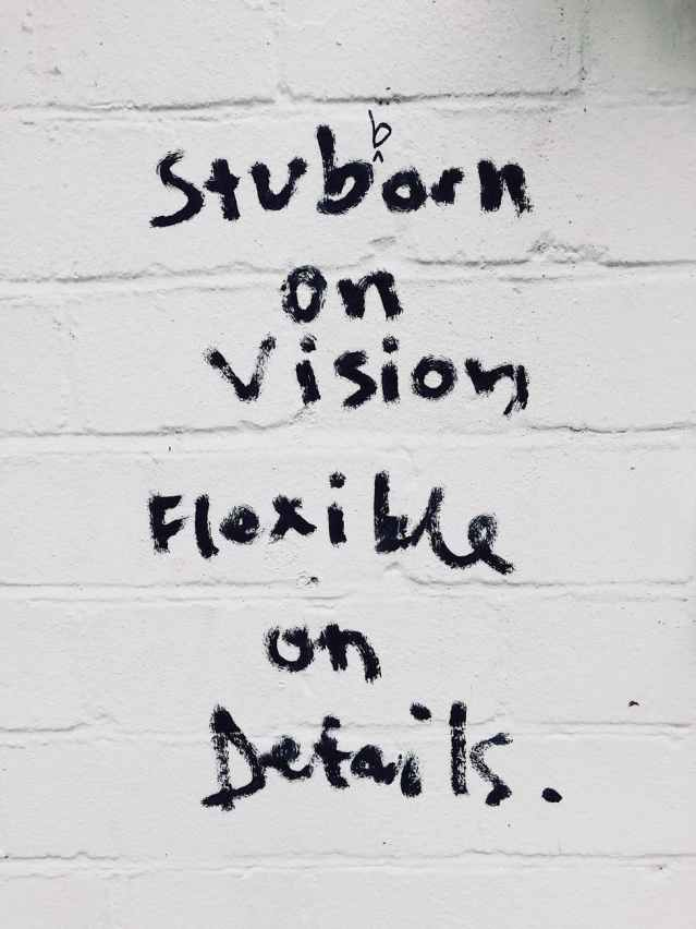 "Black writing on wall saying ""Stubborn on vision, flexible on details,"" to demonstrate brevity in business writing skills."