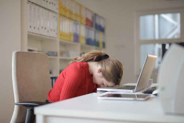 A woman sin a red sweater with her head resting on her laptop as she is tired and working remotely from home.