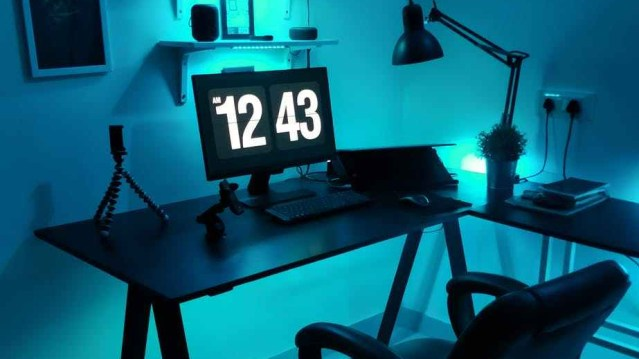 Flat screen computer monitor on a wooden desk that shows the time, 12:43 am displayed on the screen to show someone who is working from home late in the night.