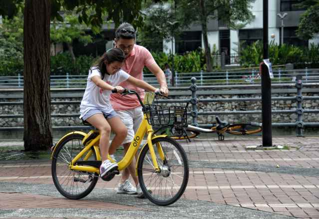 A dad teaching his daughter how to ride a bike by holding her bicycle and helping her ride.