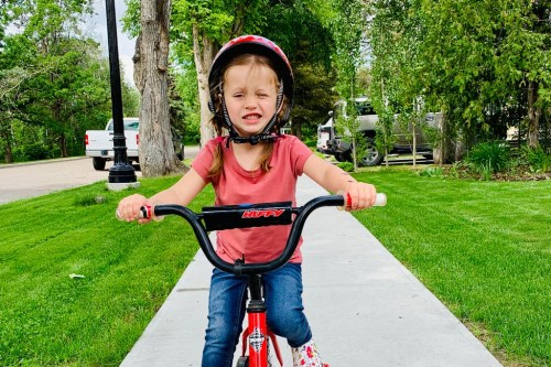 Small girl wearing a red helmet and riding a red bike on the sidewalk with green trees and grass in the background.