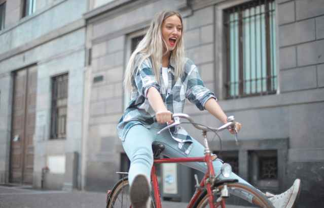 Young girl in blue jeans and a blue and white checkered top having fun while riding a red bicycle with her legs off the pedals.