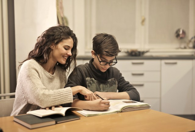 Woman in a white top helping her young son with his homework and they look at his books.