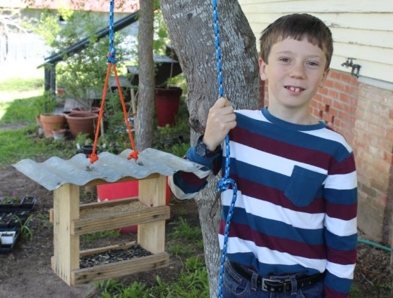 Eli's skills are not limited to plant propagation. Here he proudly displays a birdhouse he designed and built.