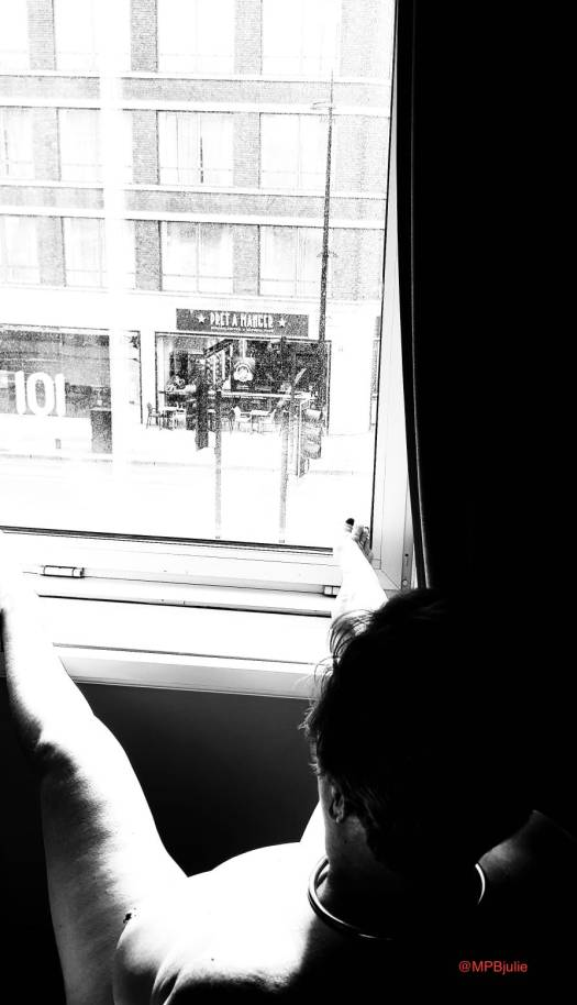 I am leaning back in a chair facing the window. My left breast is visible, I have my legs spread and feet on the window ledge. This photo is in black and white