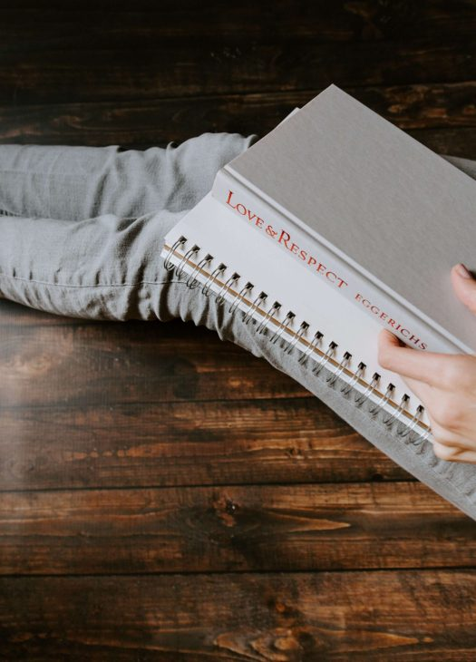 Person with a notebook and grey book entitled love and respect on her lap.