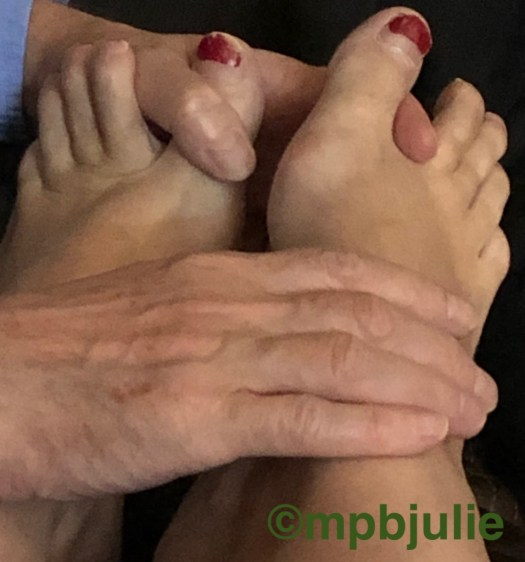 He is holding my feet in both hands, one with fingers between my toes, and the other hand on top.