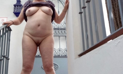 Me standing on the stairs of our apartment in Seville. I have my dress pulled up over my boobs. I am naked under my dress.