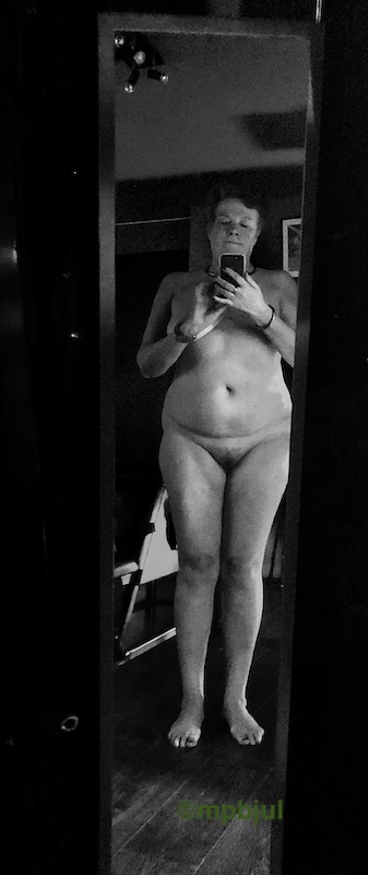 Standing naked infront of a mirror. The image is black and white and was taken at a dungeon.