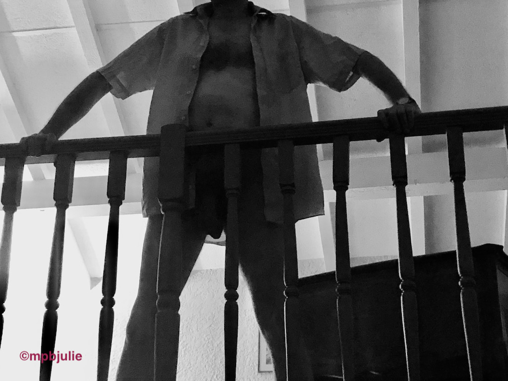 Master standing at the railings of the mezzanine floor of an apartment we stayed in this summer.