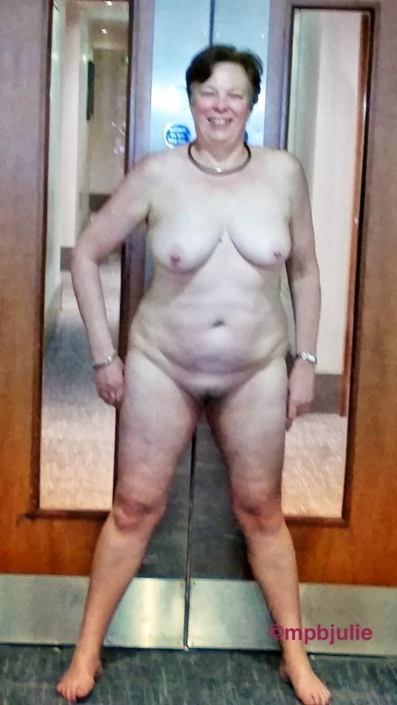Standing in front of some fire doors in a hotel corridor.