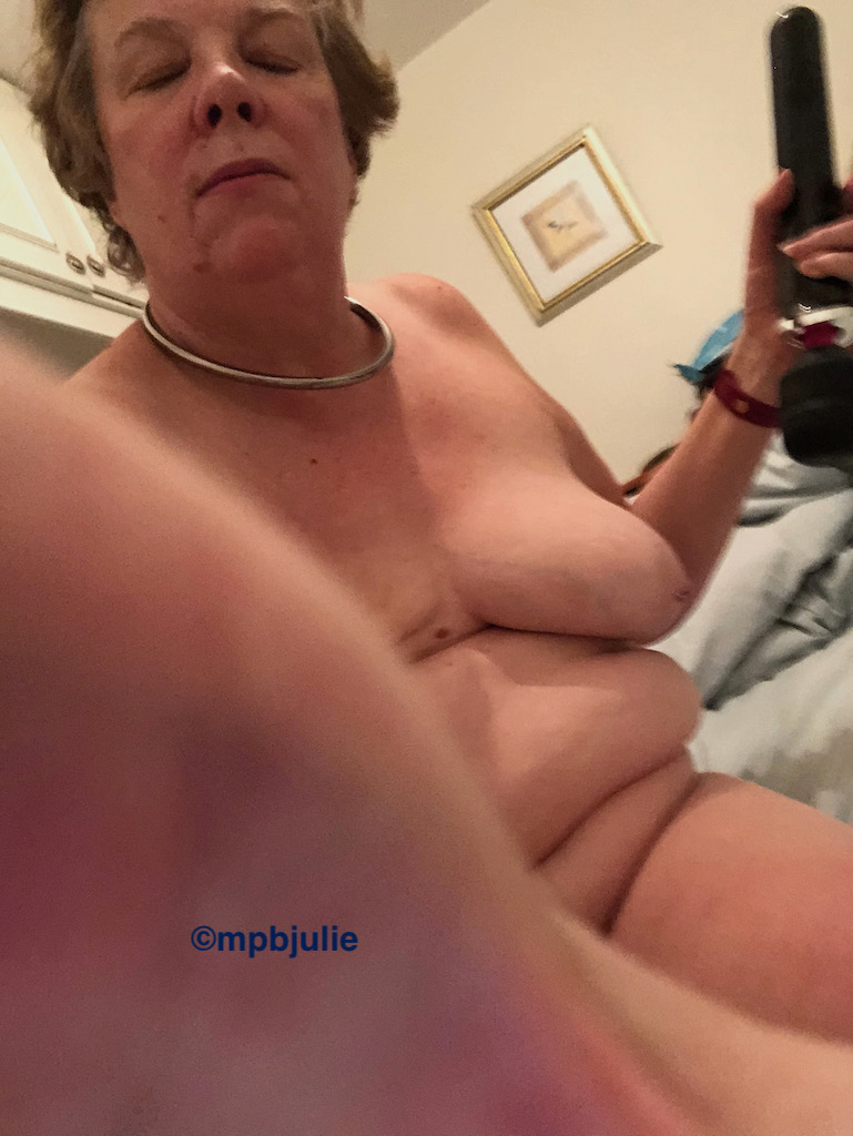 I am sitting naked in bed. My right knee partially obscures my right side. I am holding a vibrator in my left hand. My eyes are closed.
