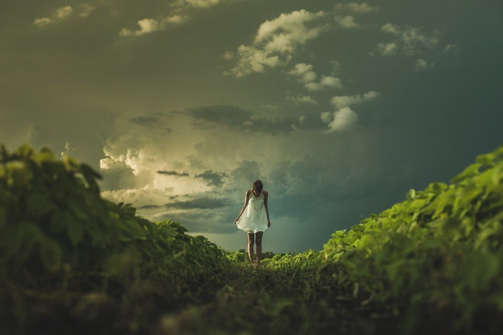 A girl stands between two hills, she seems to be close to the sky