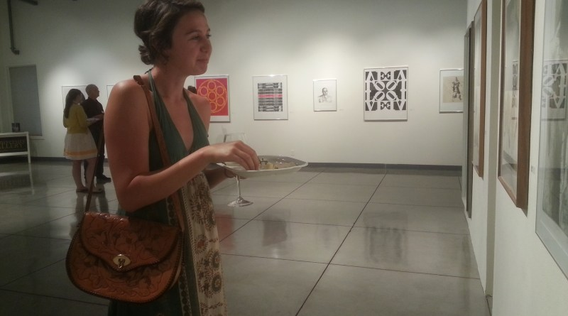"""Senior Lili Fischer looks at a piece titled Captive by Keith Achepohl. The exhibit """"To Be Human"""" opened Wednesday night in the University Gallery in Ingram Hall.  Photo by Leah Traxel."""