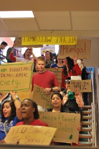 "Students march through Anderson University Center as part of the International Workers' Day protest at PLU on Wednesday morning.  They hold cardboard signs made by members of the student group Students of the Left and shout cheers such as ""What's disgusting? Union busting!"""