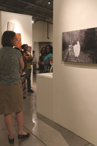 """A woman studies the photograph by senior Jaeda Reed. REed specializes in photography and featured a number of pieces in """"Unfiltered."""""""