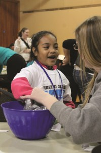 This Kent School District student participates in a fun learning activity led by a PLU student.  She is part of the Kinder to College program that visited campus.