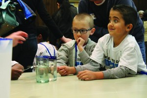 Kindergarteners learn about different sounds made when tapping on glasses filled with water.  Kindergarteners from the Kent school district wisited campus and participated in activities led by PLU students such as this one on Tuesday.