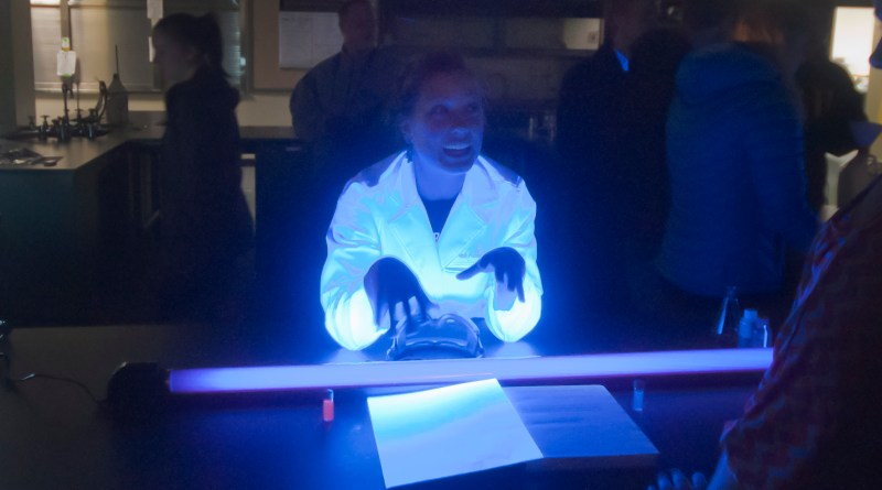 Marisa Adams used a blacklight to do an experiment Tuesday at the Mole Day Eve Spooktacular October 23.  Adams is the Vice President of the Chemistry Club, which put on the event.  Photo by Joshua Aten.