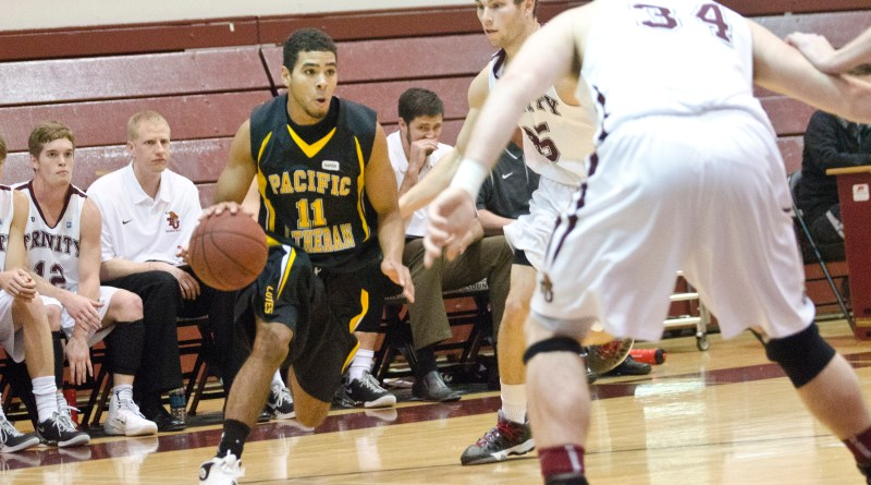 Guard Daniel Landram, a junior, dribbles between two Trinity defenders. Landram led the Lutes with 12 points. Photo by Jesse Major.