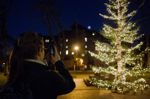 "Sophomore Madison Thackana takes a photo with her phone at the annual Light Up Red Square event Tuesday evening. After the tree lighting, attendees sang ""Joy to the World."" Light Up Red Square is an annual Christmas tradition at PLU. Photo by Jesse Major"