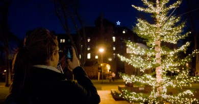 """Sophomore Madison Thackana takes a photo with her phone at the annual Light Up Red Square event Tuesday evening. After the tree lighting, attendees sang """"Joy to the World."""" Light Up Red Square is an annual Christmas tradition at PLU. Photo by Jesse Major"""