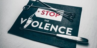 "Paper sign with the text ""Stop the Violence."" Opinion article."