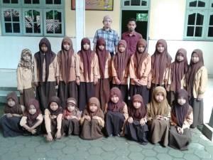 BERSAMA: Kepala SMP Al-Asy'ari (baju merah, tanpa kopiah) foto bersama salah seorang guru dan siswinya beberapa waktu lalu. (Foto Sya'roni for Mata Madura)