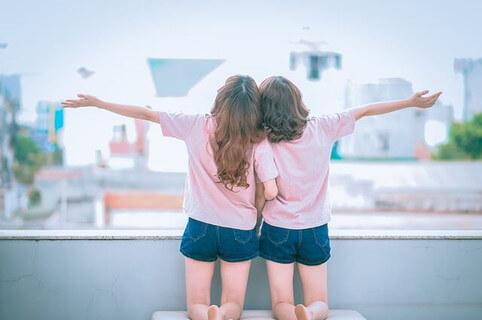 バルコニーから外へ向かって手を広げる若い女の子2人
